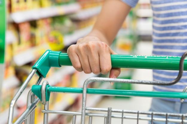 Vrouw die in supermarkt winkelt Premium Foto