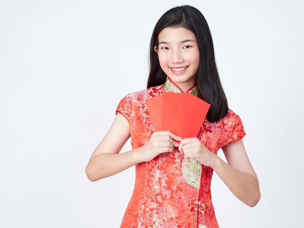 Vrouw die in traditionele chinese kleding rode envelop houdt Premium Foto