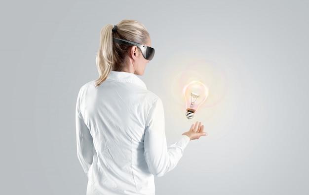 Vrouw die in virtuele werkelijkheidsglazen aan het geïsoleerde hologram kijkt. Premium Foto