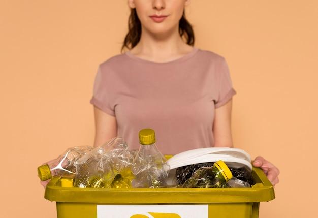 Vrouw die in vrijetijdskleding herbruikbare recyclingsdoos draagt Gratis Foto