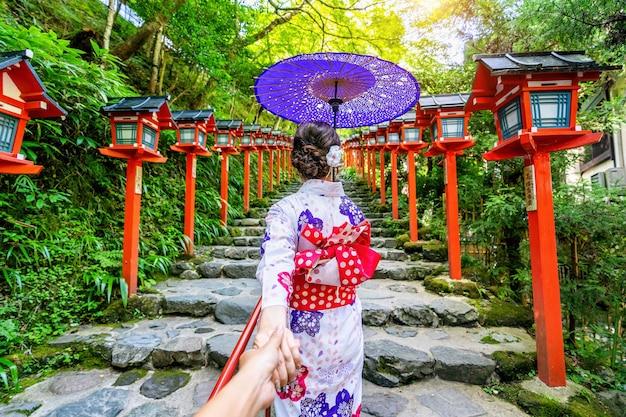 Vrouw die japanse traditionele kimono draagt die de hand van de man vasthoudt en hem leidt naar het heiligdom van kifune, kyoto in japan. Gratis Foto