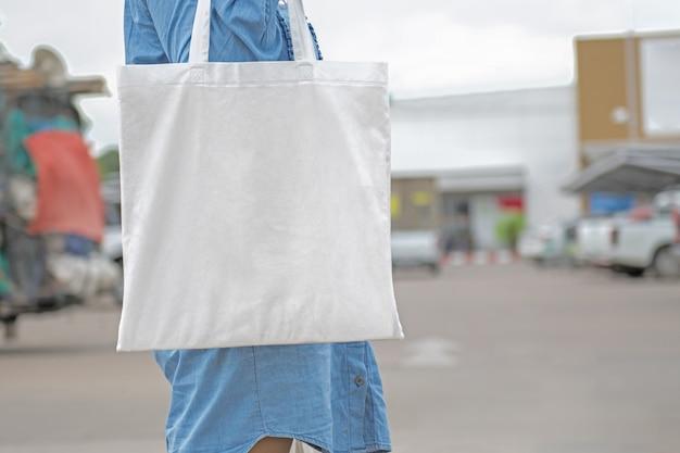 Vrouw die katoenen zak voor het winkelen houdt. eco concept Premium Foto