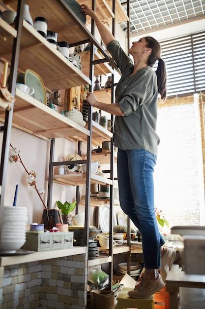 Vrouw die keramiek op plank zet Premium Foto