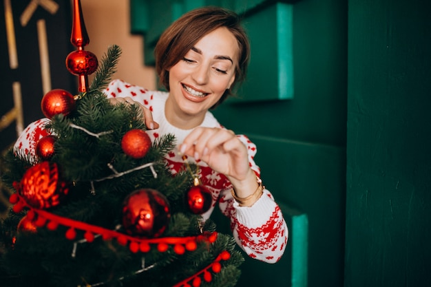 Vrouw die kerstboom met rode ballen verfraait Gratis Foto
