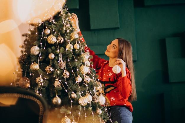 Vrouw die kerstmisboom op kerstmis verfraait Gratis Foto