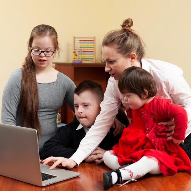 Vrouw die kinderen met benedensyndroom iets op laptop tonen Gratis Foto