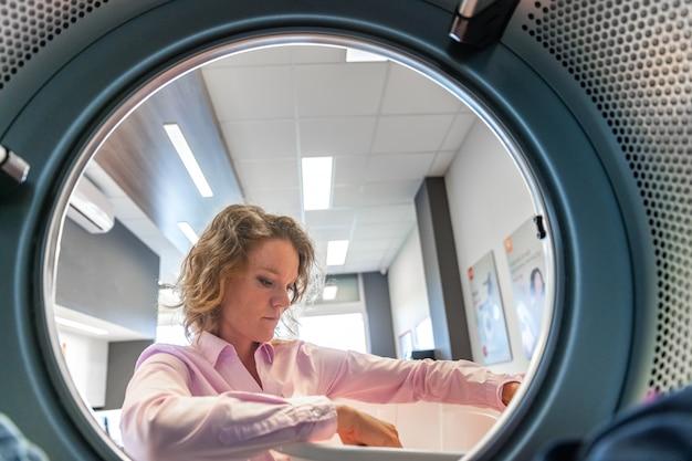Vrouw die kleren opneemt in een droger in een openbare wasserij Premium Foto