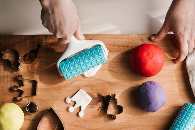 Vrouw die kleurrijke plasticine op houten raad vormen Gratis Foto