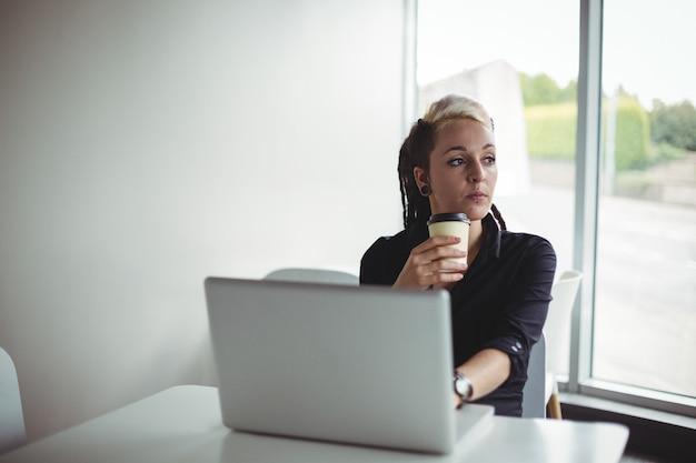Vrouw die koffie heeft terwijl het gebruiken van laptop Gratis Foto