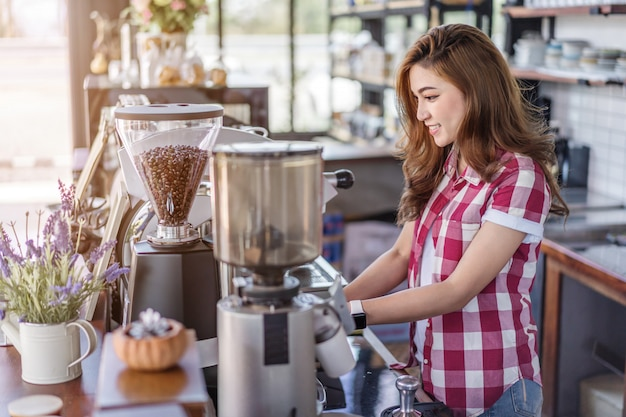 Vrouw die koffie met machine in koffie voorbereidt Premium Foto