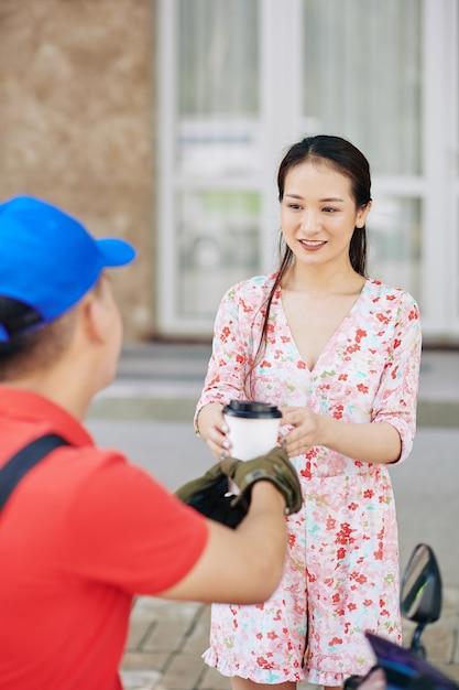 Vrouw die kopje koffie ontvangt Premium Foto
