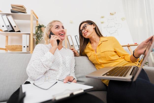 Vrouw die laptop houdt en haar collega bekijkt Gratis Foto