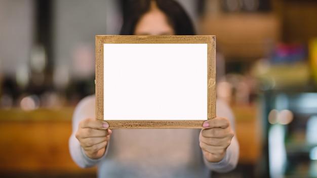 Vrouw die leeg houten frame in koffiewinkel houdt Premium Foto