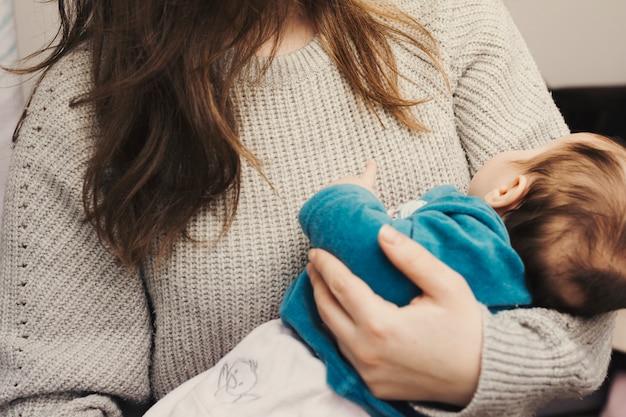 Vrouw die leuke baby in wapens houdt Gratis Foto