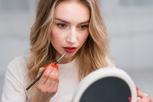 Vrouw die lippenmake-up met spiegel doet Gratis Foto