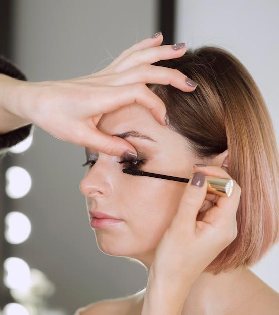 Vrouw die mascara op mooi model toepast Gratis Foto