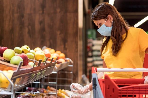 Vrouw die medisch masker draagt dat fruit koopt Premium Foto