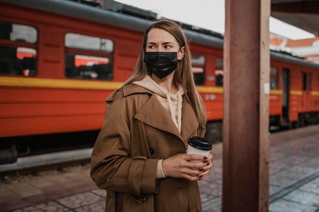 Vrouw die medisch masker draagt in een treinstation Gratis Foto
