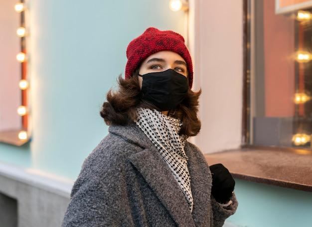 Vrouw die medisch masker in de stad draagt Gratis Foto
