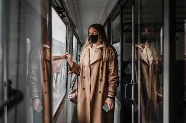 Vrouw die medisch masker in een trein draagt Gratis Foto