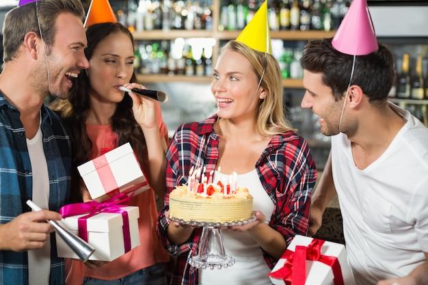 Vrouw die met cake in handen glimlacht Premium Foto