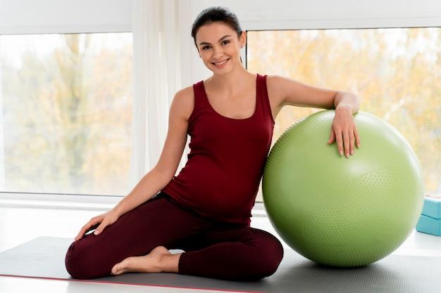 Vrouw die met geschiktheidsbal uitoefent terwijl zij zwanger is Gratis Foto