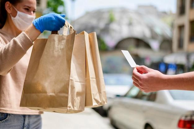 Vrouw die met gezichtsmasker het winkelen zakken ontvangt Premium Foto