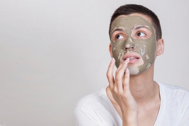 Vrouw die met gezichtsmasker omhoog kijkt Gratis Foto