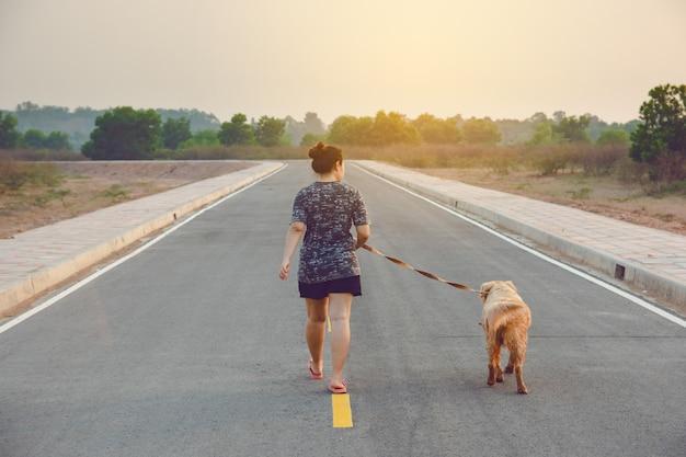 Vrouw die met haar golden retrieverhond op de openbare weg loopt. Premium Foto
