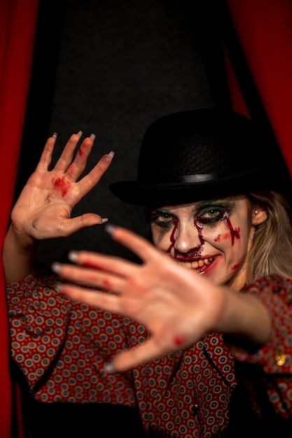 Vrouw die met halloween-jokermake-up camera en het verbergen bekijken Gratis Foto