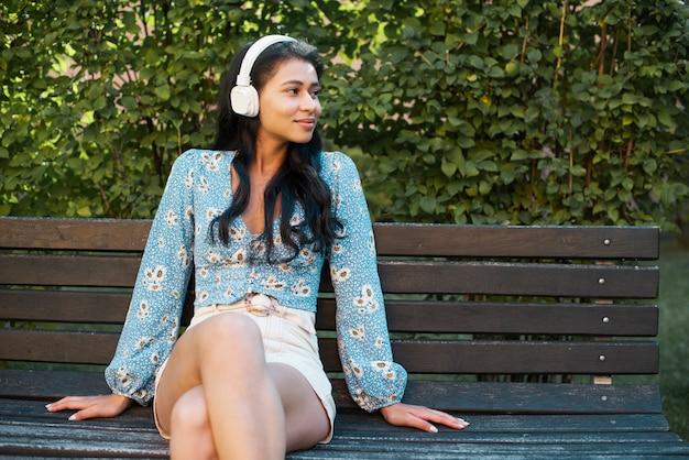 Vrouw die met hoofdtelefoons op een bank zit Gratis Foto
