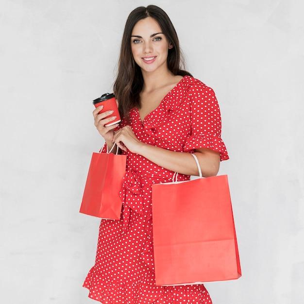 Vrouw die met koffie en het winkelen zakken aan de camera glimlacht Gratis Foto