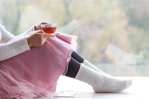 Vrouw die met kop thee gebreide sweaterzitting thuis door het venster draagt Premium Foto