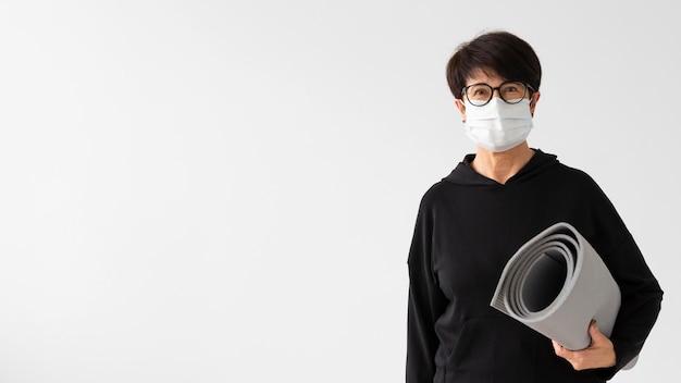 Vrouw die met medisch masker een geschiktheidsmat houdt Gratis Foto