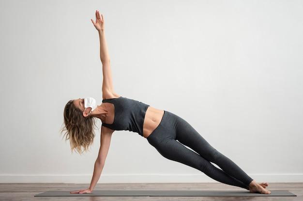 Vrouw die met medisch masker thuis yoga doet Gratis Foto