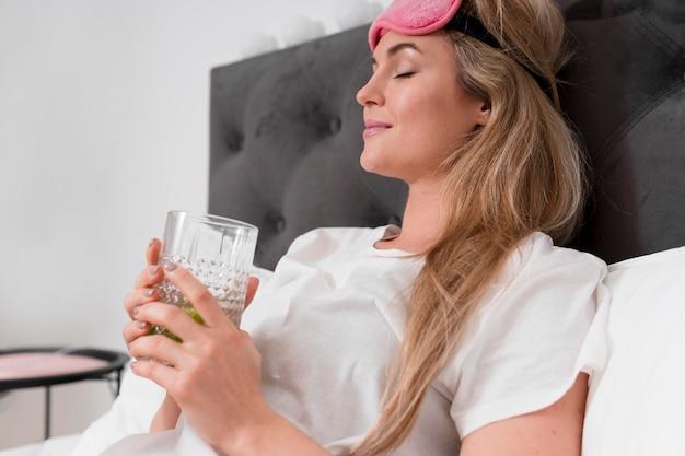 Vrouw die met slaapmasker een glas water houdt Gratis Foto