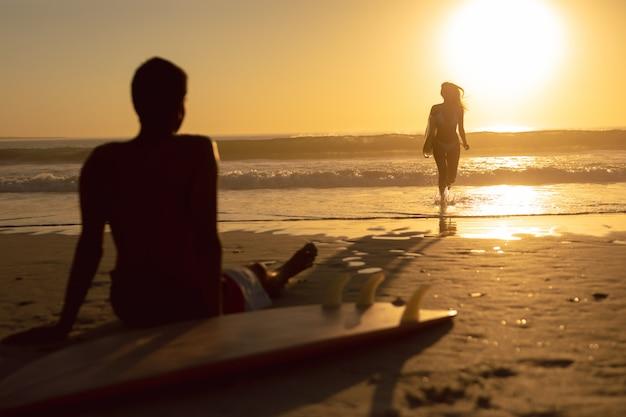 Vrouw die met surfplank loopt terwijl man het ontspannen op het strand Gratis Foto