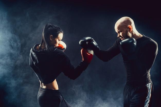 Vrouw die met trainer bij boksen en zelfverdedigingsles uitoefent vrouwelijke en mannelijke strijd Premium Foto