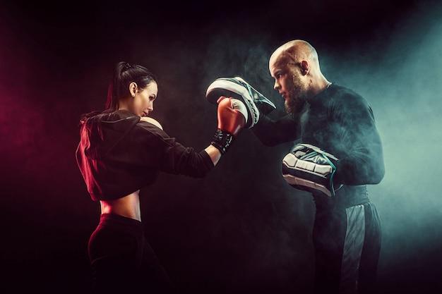 Vrouw die met trainer bij het in dozen doen en zelfverdedigingsles uitoefenen Premium Foto
