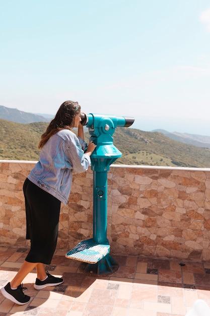 Vrouw die met verrekijkers kijkt Gratis Foto