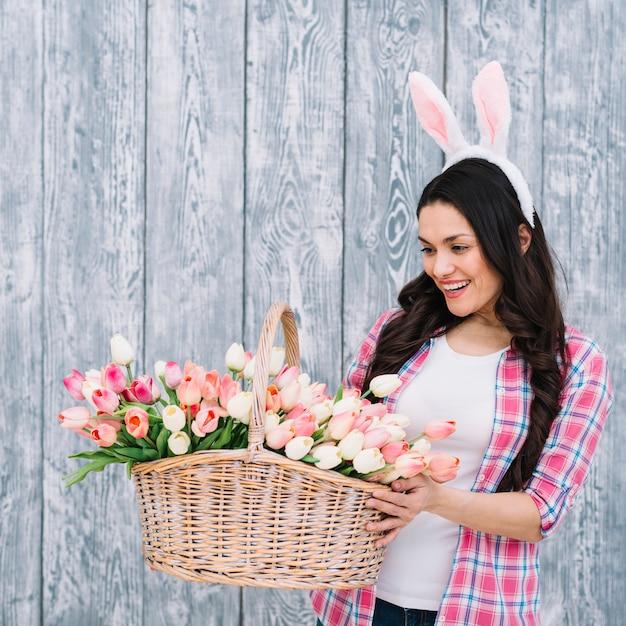 Vrouw die met witte konijntjesoren mand van tulpen bekijken tegen grijze houten plank Gratis Foto