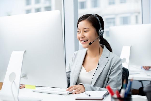 Vrouw die microfoonhoofdtelefoon draagt die in call centrebureau werkt Premium Foto