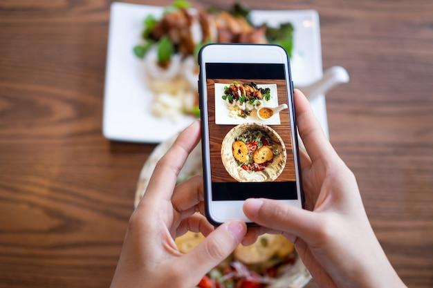 Vrouw die mobiele telefoon met behulp van om foto's van voedsel op de lijst te nemen. op mobiel genomen en op sociale netwerken gezet. Premium Foto