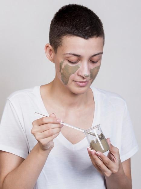 Vrouw die modderbehandeling op gezicht toepast Gratis Foto