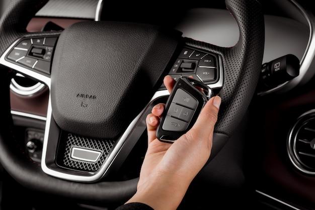 Vrouw die moderne autosleutel, alarmsysteem en stuurwiel met elektrische knopen houdt Premium Foto