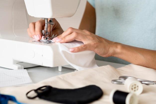 Vrouw die naaimachine voor gezichtsmasker gebruikt Gratis Foto