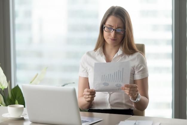 Vrouw die naar beneden financiële indicatoren analyseren Gratis Foto
