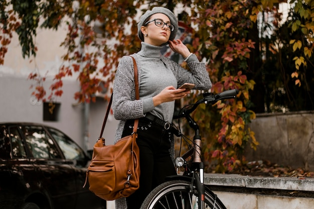 Vrouw die naast haar fiets loopt Gratis Foto