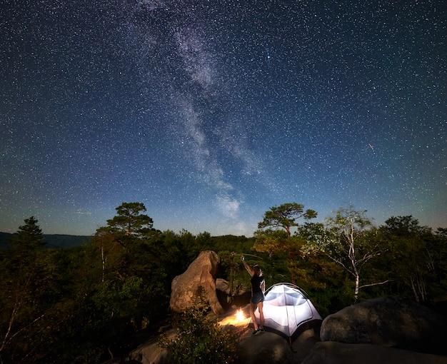 Vrouw die naast kamp, vuur en toeristentent bij nacht rust Premium Foto