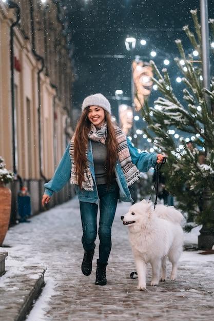 Vrouw die neer met witte hond loopt Gratis Foto